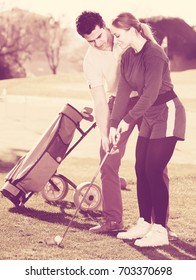 Golf Coach helping a young girl prepare for the game of golf