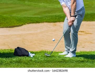 Golf Coach hitting golf ball. No face, Sand splashing.