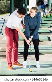 Golf Coach tells a young girl how to hit the golf ball