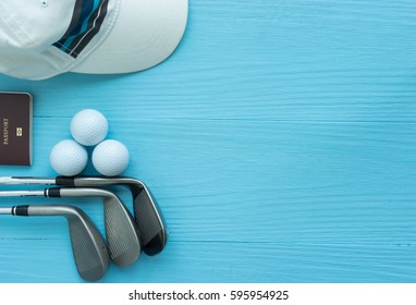 Golf concept : cap, golf balls, golf clubs, passport on wooden table. Top view with copy space.