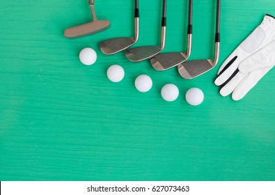 Golf concept : glove, golf balls, golf clubs on wooden table. Flat lay with copy space.