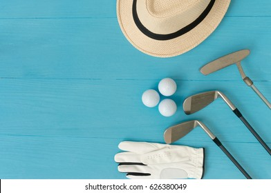 Golf concept : panama hat, glove, golf balls, golf clubs on wooden table. Flat lay with copy space.