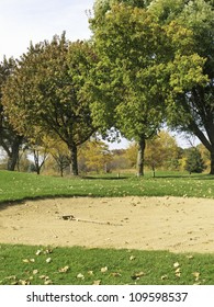 Golf course in autumn: Fairway bunker and nearby trees, with flag in middle ground, northern Illinois in October