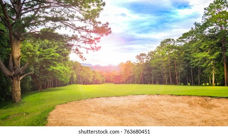 Golf course is beautiful layout and green golf on dark evening atmosphere. Golfers can see  beautiful fairway and bunker sand . There are beautiful sky and cloud with  green forest fresh and enjoy.