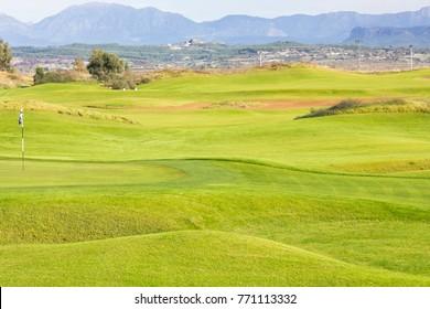 Golf course in Belek. Green grass on field. Blue sky, sunny day