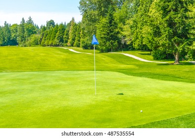 Golf course and a blue flag in a sunny day. Canada, Vancouver.