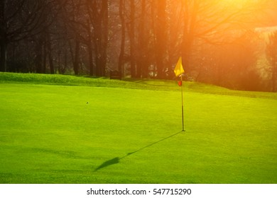 Golf course in the countryside. Green field with a flagstick