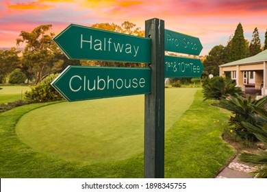 Golf course direction signs on fairway and colourful sunset in the background