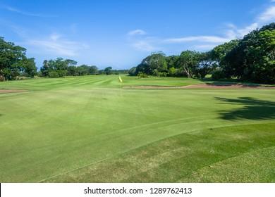 Golf course fairway hole flagstick green trees scenic summer coastal course.
