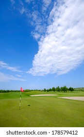 Golf course and flag. Blue and cloudy sky.
