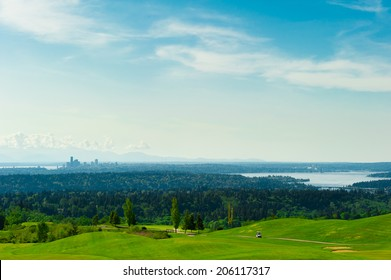 Golf course with green grass and Seattle downtown at the background. A relaxing and fun activity for weekends.