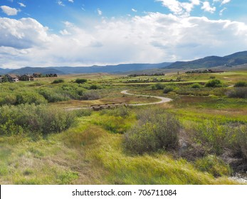 A golf course on a prairie in Colorado.  The course is next to a housing development. There are mountains in the background and a clear blue sky overhead with white puffy clouds.