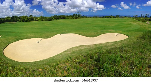 Golf course panorama with sand bunkers over blue sky