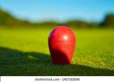 Golf course red ball on the grass field background unique golfing decoration. Bournemouth Queens Park Golf Course, Dorset, England. UK Luxury Sport Recreation Lifestyle