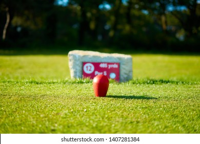 Golf course red ball on the grass field background unique golfing decoration. Bournemouth Queens Park Golf Course, Dorset, England. UK Luxury Sport Recreation Lifestyle. Sport event advertising image.