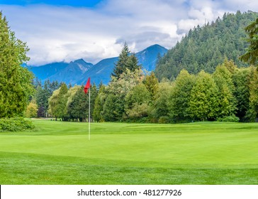 Golf course with red flag in front and mountains on background.