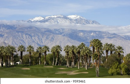 A golf course sits prettily in front of palm trees and snow capped mountains.