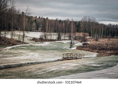 Golf course in winter, closed and abandoned until next season. Ice and snow on the fairway.