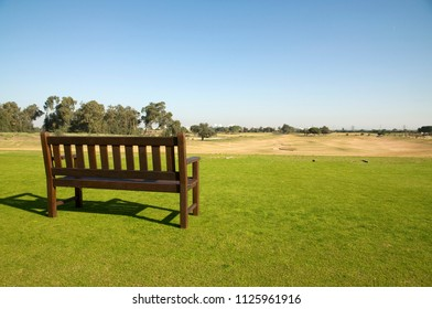 Golf course with wood bench