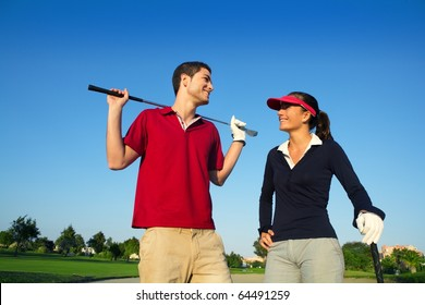 Golf course young happy players couple talking posing on bunker