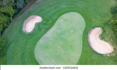 Golf court from dron on bird eye view with hole and sand trap all around court