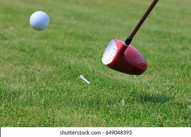 Golf Driver Club Hitting Ball off a Tee on a Golf Course Fairway.