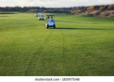 Golf electric cars riding on a golf course in the sunny day, golf carts drive with golfers in resort club