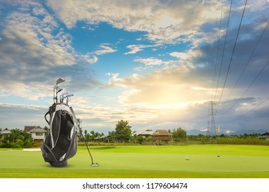 Golf equipment and golf bag , putter, ball on green sunset as background