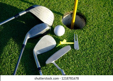 Golf equipment on green grass. Golf putters and tee on the green golf course.