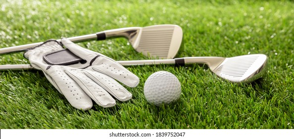 Golf equipment, sticks, glove and golfballs on green course lawn, close up view, banner. Golfing sport and club concept