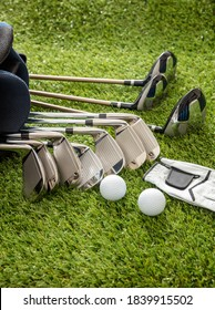 Golf equipment, sticks set in a bag glove and golfballs on green course lawn, close up vertical view. Golfing sport and club concept