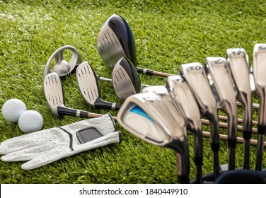 Golf equipment, sticks set in a bag glove and golfballs on green course lawn, close up view. Golfing sport and club concept