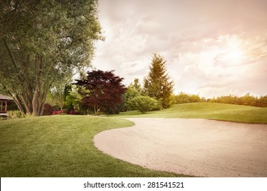 Golf fairway with sand bunker and beautiful sky at sunset.