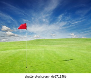 Golf field with red flag in the hole