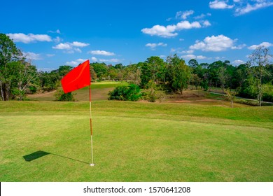 Golf flag in golf course, beautiful fairway and layout field on blue sky background, red flag on hole for symbol of golfer to playing in summer vacation, tree side fairway of lawn