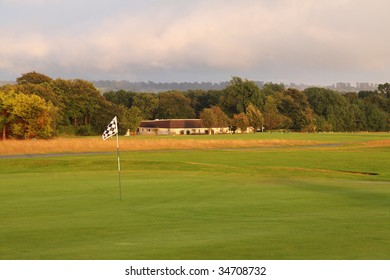 A golf flag at dusk with a clubhouse in the background