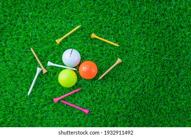 Golf glove ,colorful ball ,tee and gold club put on green grass of golf course ,This objects for play - Shutterstock ID 1932911492