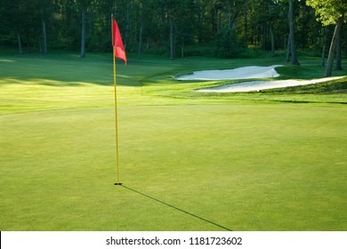 Golf green with red flag bordered by white sand traps and trees in late afternoon sun