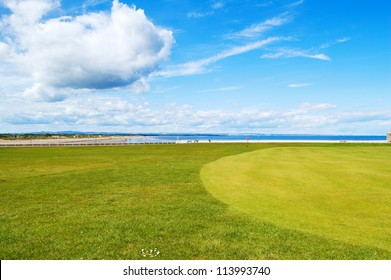 Golf green St Andrews old course links, on background West Sands beach movie location Chariots of Fire. Fife, Scotland, Uk, Europe.