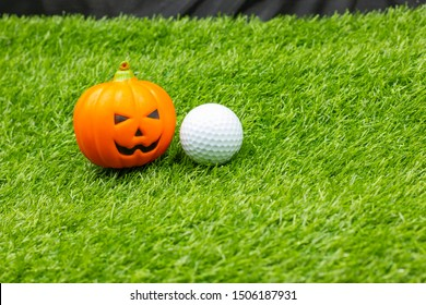 Golf Halloween with golf ball and pumpkins are on green grass