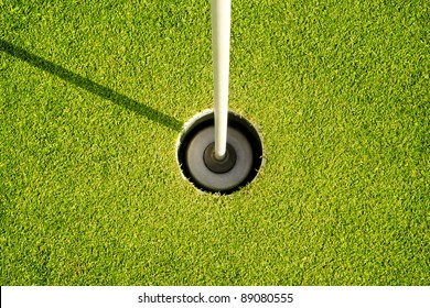 Golf hole and flag with the green grass