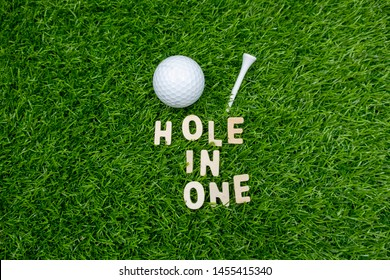 Golf hole in one with golf ball and tee on green grass.