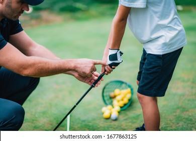 Golf Instructor adjusting young boy's grip