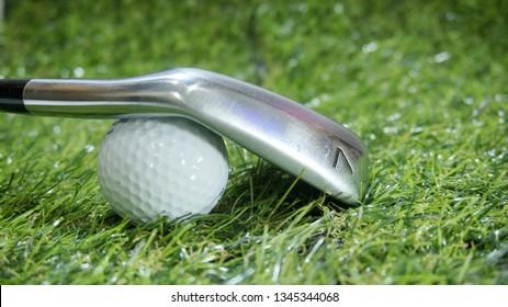 Golf iron and ball on green grass - iron 7