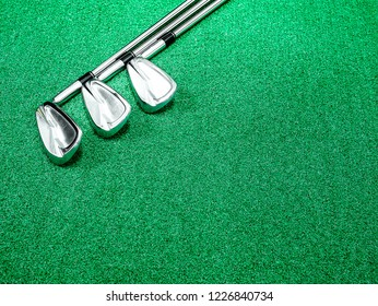 Golf iron clubs placed on artificial grass with space for text or sentence.