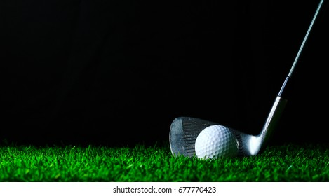 Golf iron and golf-ball on green grass