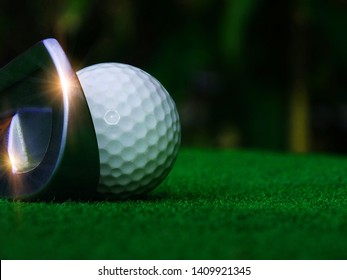 The golf iron on the field where the players are going to put a swing to hit the white golf ball closely on the natural background. The green golf course And the sun shines