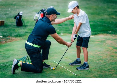 Golf Lessons. Golf instructor giving game lesson to a young boy.
