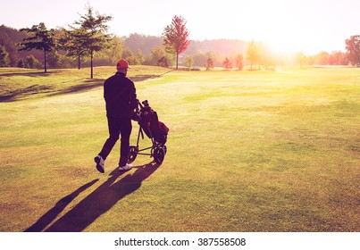 Golf man player walking on fairway with trolley and clubs during sunset in golf curse.