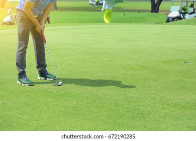 Golf man putting on green for birdie while on vacation.